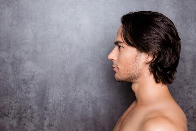 Ritratto di vista laterale del giovane con i capelli neri vicino al muro grigio