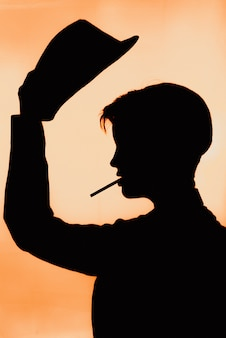 Ritratto di una silhouette di una ragazza in un cappello con una sigaretta.