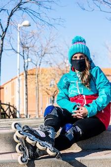 Ritratto di una ragazza di pattinaggio con una maschera per il viso. vestito con una giacca blu e un berretto di lana blu. ginocchiere e pattini. concetto di pattinaggio in linea