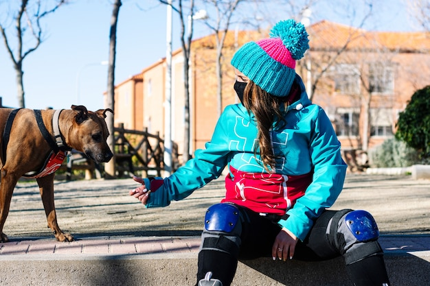Ritratto di una ragazza di pattinaggio con una maschera e il suo cane. vestito con una giacca blu e un berretto di lana blu. ginocchiere e pattini. concetto di pattinaggio in linea