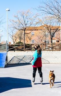 Ritratto di una ragazza di pattinaggio con una maschera per il viso pattinaggio con il suo cane. vestito con una giacca blu e un berretto di lana blu. ginocchiere e pattini. concetto di pattinaggio in linea