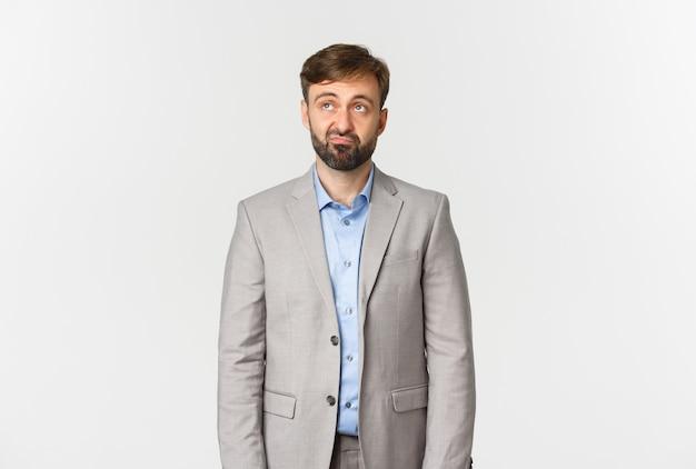 Ritratto di impiegato maschio barbuto scettico e sconvolto in abito grigio