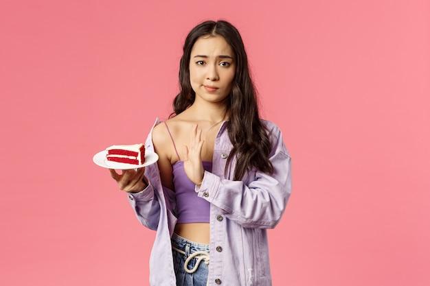 Ritratto di giovane scettica elegante ragazza esile asiatica che rifiuta di mangiare la torta, smirk mostra il segno superiore al dessert sdraiato sul piatto, rifiutando provalo, deluso dal cattivo gusto, stand