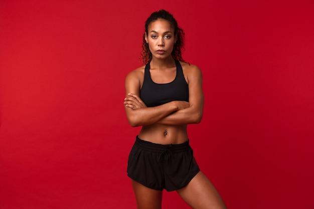 Ritratto di magrissima sportiva afroamericana in abiti sportivi neri in piedi, isolata sopra la parete rossa