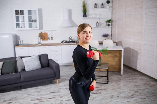 Il ritratto di una donna snella fa sport a casa, con indosso i suoi vestiti fitness top e leggings. fitness a casa per un bel corpo. esercizi con manubri per il corpo femminile