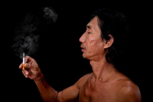 Il ritratto del vecchio magro stava fumando sullo sfondo nero