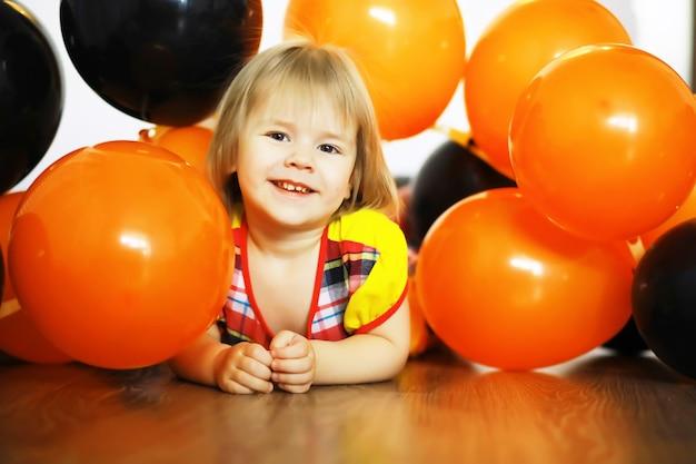Ritratto di un bambino piccolo sdraiato sul pavimento in una stanza decorata con palloncini. concetto di infanzia felice.