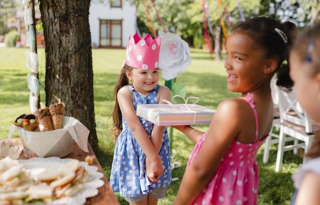 Un ritratto di piccola ragazza con amici e regali all'aperto in giardino in estate.
