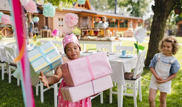 Ritratto di piccola ragazza con molti regali all'aperto in giardino in estate.