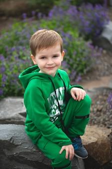 Ritratto di un piccolo ragazzo sorridente sullo sfondo di un parco in fiore