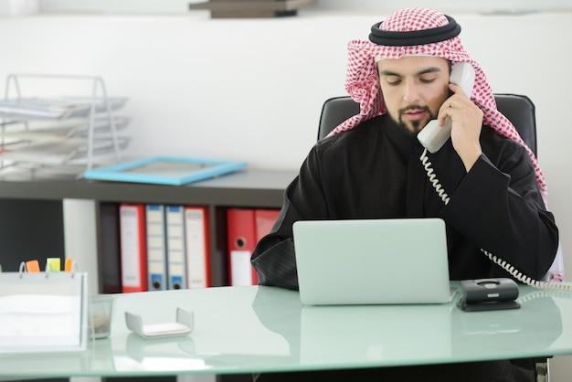 Ritratto di un uomo d'affari arabo intelligente che usa il laptop e parla al telefono Foto Premium