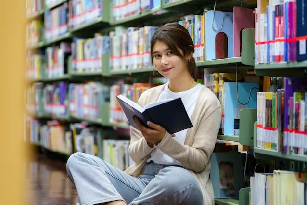 Ritratto del libro di lettura dello studente universitario della donna asiatica intelligente e che guarda l'obbiettivo tra gli scaffali per libri nella biblioteca del campus con copyspace.