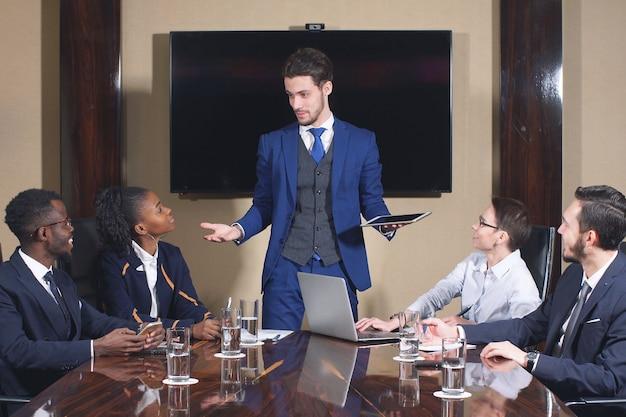 Ritratto dei soci commerciali astuti che per mezzo del computer portatile alla riunione.