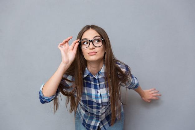 Ritratto di una bella ragazza investigativa intelligente in camicia a quadri con i capelli lunghi con gli occhiali sul muro grigio