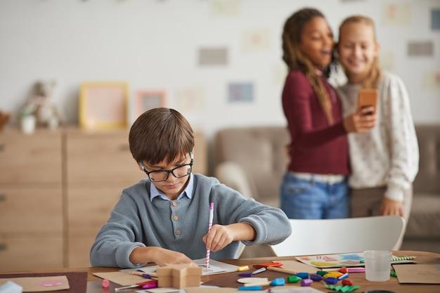 Ritratto di smart little boy tracciando forme mentre si disegna n arte e classe di artigianato con ragazze divertendosi in background, copia dello spazio