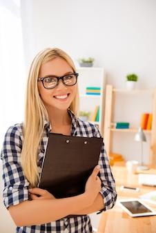 Ritratto di donna intelligente in bicchieri tenendo la cartella con i documenti