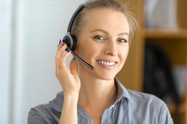 Ritratto di una donna sorridente con auricolare che lavora in un call center. avvicinamento.