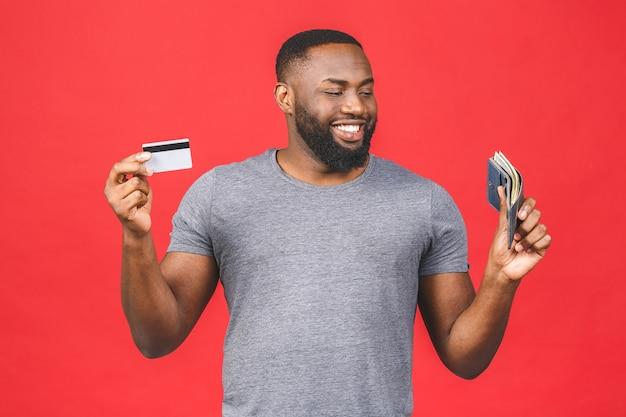 Ritratto di un uomo barbuto nero afroamericano sorridente che mostra la carta di credito e il portafoglio con i soldi