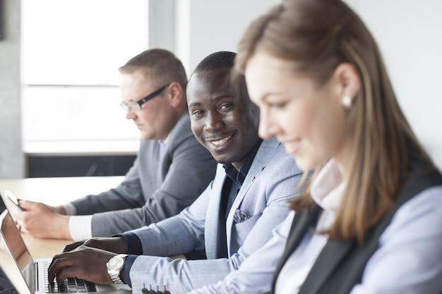 Ritratto di un uomo d'affari afroamericano sorridente con dirigenti che lavorano in background