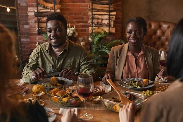 Ritratto di sorridente coppia afro-americana godendo la cena con gli amici in un'illuminazione accogliente