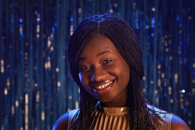 Ritratto di sorridente ragazza afro-americana guardando la fotocamera mentre in piedi su sfondo scintillante alla festa, copia spazio