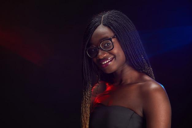 Ritratto di sorridente ragazza afro-americana con gli occhiali mentre posa alla festa, copia spazio