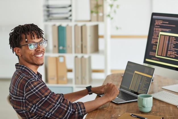 Ritratto di sorridente afro-americano sviluppatore it guardando la fotocamera durante la digitazione sulla tastiera con codice di programmazione nero e arancione sullo schermo del computer e laptop, spazio di copia