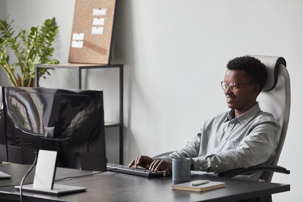 Ritratto di un uomo afroamericano sorridente che utilizza il computer mentre è seduto alla scrivania in ufficio, concetto di sviluppatore di software, spazio di copia