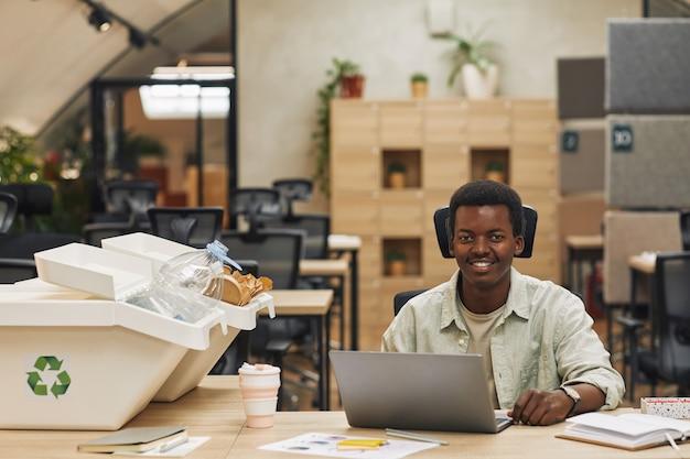 Ritratto di sorridere afro-americano uomo con laptop mentre seduto da bidoni per la raccolta differenziata in ufficio moderno, copia dello spazio