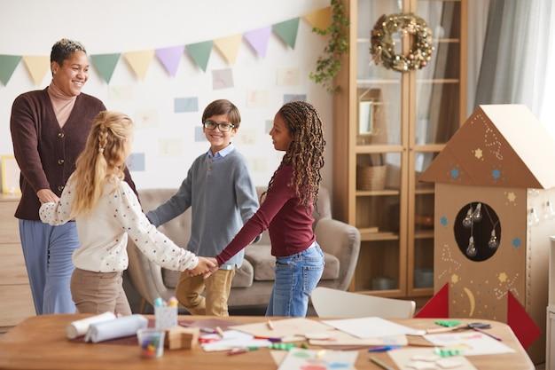 Ritratto di donna afro-americana sorridente mano nella mano con i bambini mentre balla durante la lezione a scuola, copia dello spazio