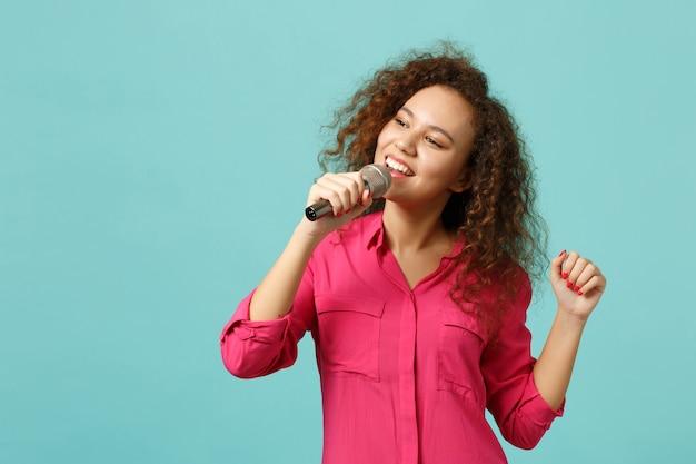 Il ritratto della ragazza africana sorridente in vestiti casuali che balla canta la canzone in microfono isolato sul fondo blu della parete del turchese in studio. persone sincere emozioni, concetto di stile di vita. mock up copia spazio.