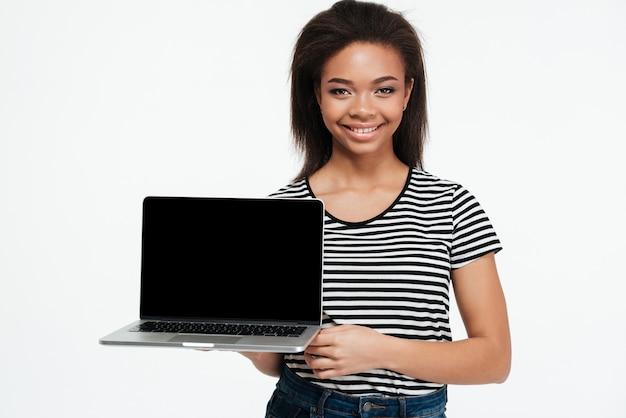 Ritratto di una donna africana sorridente che mostra il computer portatile dello schermo in bianco