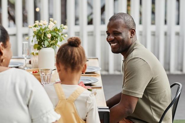 Ritratto dell'uomo afroamericano sorridente che gode della cena con la famiglia all'aperto allo spazio della copia della terrazza