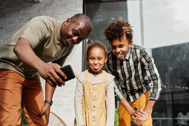 Ritratto di un uomo afroamericano sorridente che si fa un selfie divertente con due bambini all'aperto