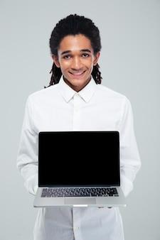 Ritratto di un uomo d'affari afroamericano sorridente che mostra lo schermo in bianco del laptop sopra la parete grigia