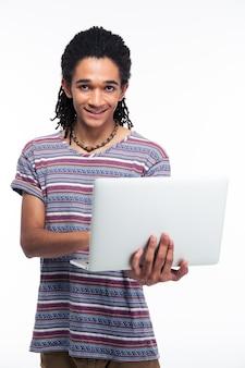 Ritratto di un uomo afroamericano sorridente che utilizza computer portatile isolato su una parete bianca