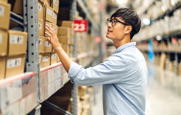 Ritratto di sorridente asiatico manager lavoratore uomo in piedi e dettagli dell'ordine controllando merci e forniture sugli scaffali