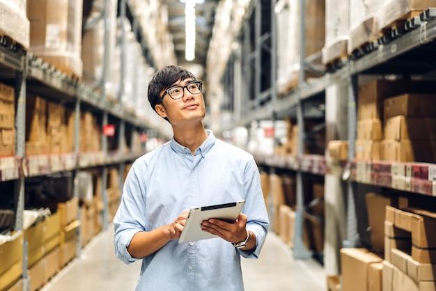 Ritratto di sorridente asiatico manager lavoratore uomo in piedi e dettagli dell'ordine su computer tablet per il controllo di merci e forniture sugli scaffali