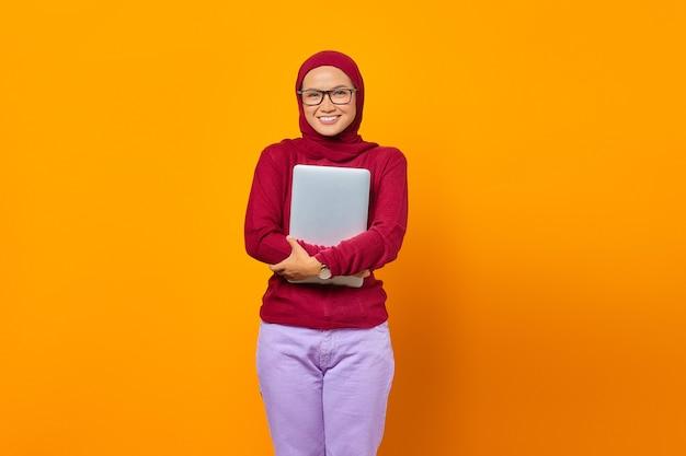Il ritratto della donna asiatica sorridente porta il computer portatile sopra fondo giallo