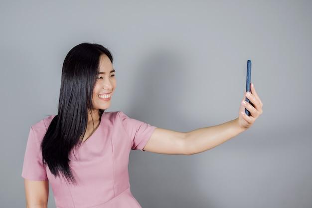Il ritratto di una donna asiatica sorridente con lunghi capelli scuri indossa un selfie su sfondo grigio