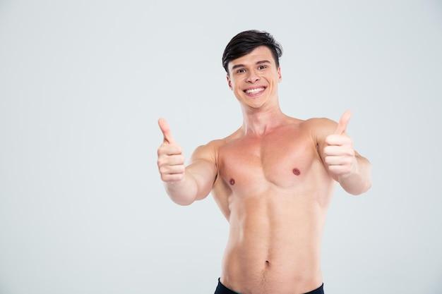 Ritratto di un uomo atletico sorridente che mostra i pollici in su isolato