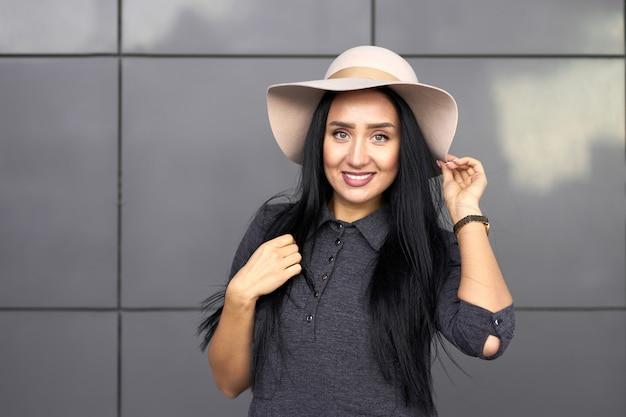 Ritratto della ragazza castana alla moda attraente sorridente che porta vestito grigio della gioventù e cappello d'avanguardia. bellissima modella in abito alla moda in piedi vicino al muro grigio