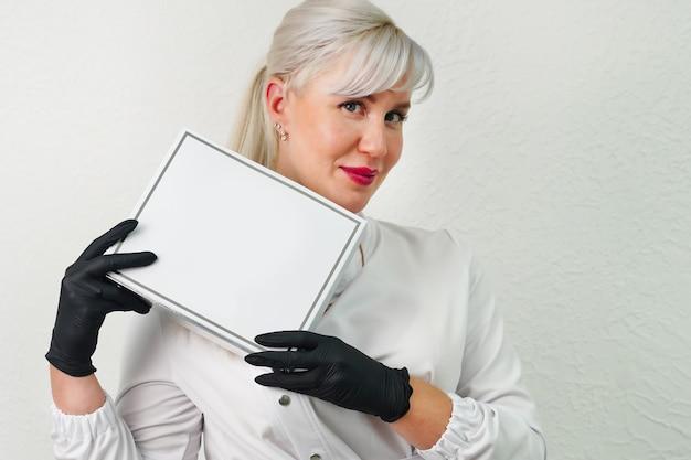 Ritratto di un medico estetista sorridente in camice bianco con in mano un vuoto vuoto una scatola bianca con un p...