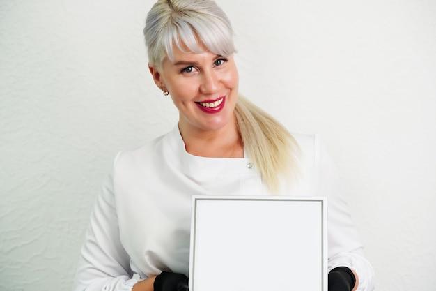 Ritratto di un medico estetista sorridente in camice bianco con in mano un vuoto vuoto una scatola bianca con un p... Foto Premium