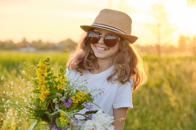 Ritratto di ragazza sorridente bambino bello in occhiali da sole cappello con bouquet di fiori di campo, tramonto in prato, ora d'oro