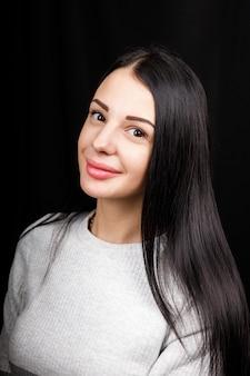Ritratto di bella donna sorridente con i capelli neri, ha un trucco minimo, guarda con calma la telecamera, indossa un maglione bianco, si erge su sfondo nero.