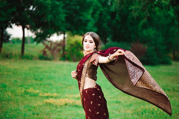 Ritratto sorridente di una bella ragazza indiana. modello di giovane donna indiana con set di gioielli rossi.