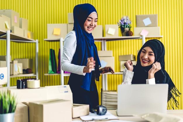 Ritratto di bei proprietari musulmani sorridenti che lavorano al computer portatile con cassette dei pacchi sul tavolo a casa