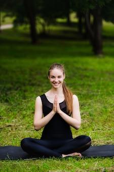 Ritratto di bella giovane donna sportiva sorridente che risolve nel vicolo del parco