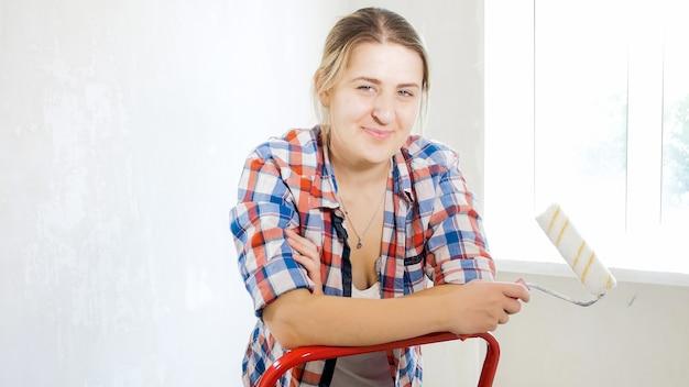 Ritratto di bella donna sorridente che tiene il rullo di vernice nella nuova casa in fase di ristrutturazione.
